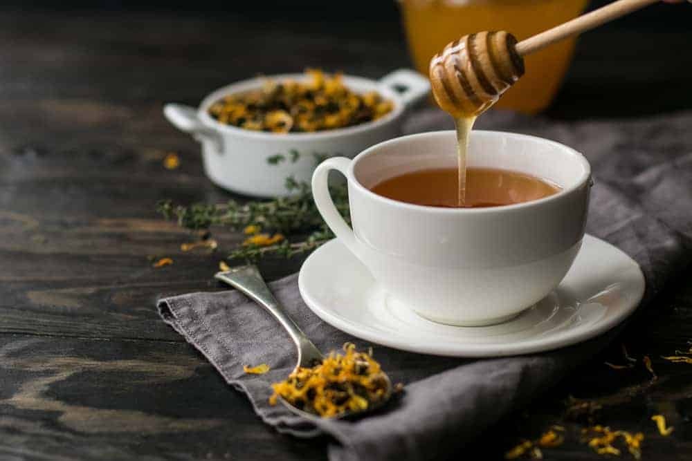 Cup with herbal tea and honey and dry herbal tea