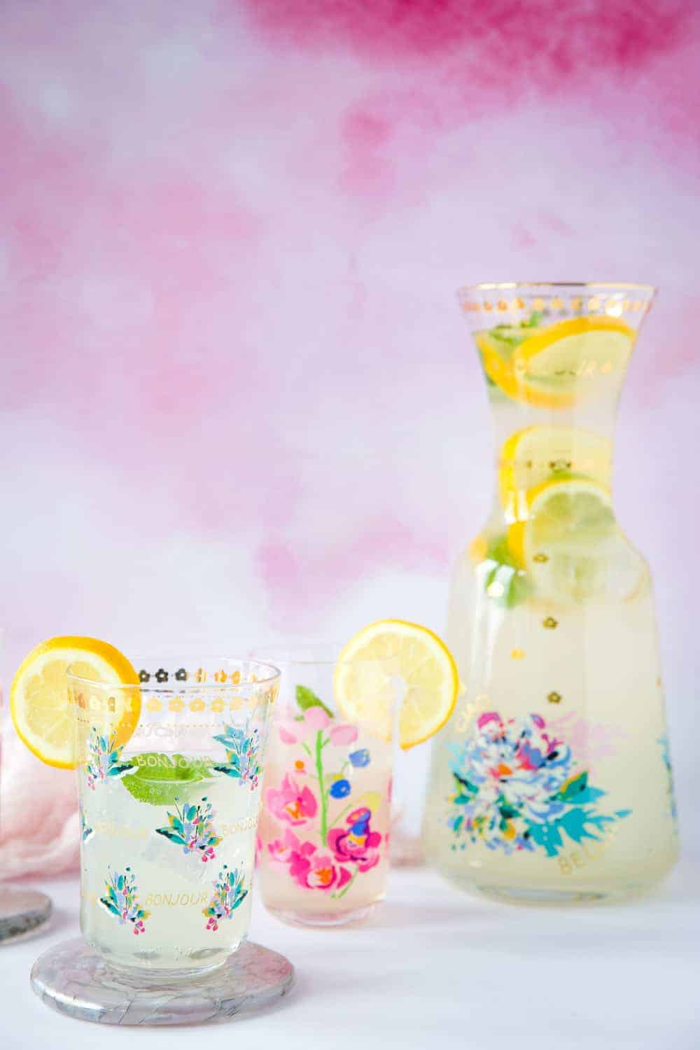A jug of lemon cordial with slices of lemon and sprigs of mint