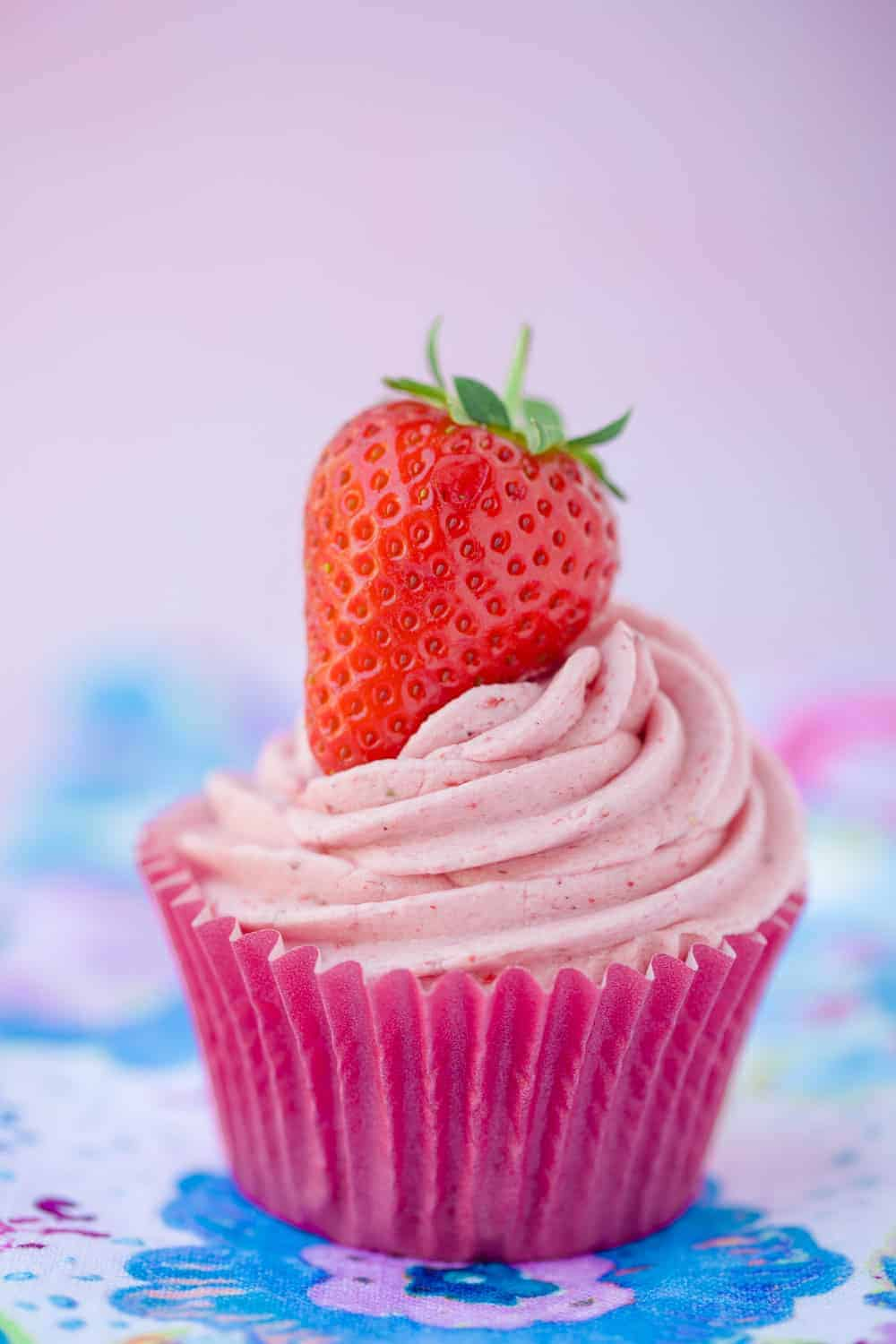 A cupcake topped with a swirl of pink strawberry frosting