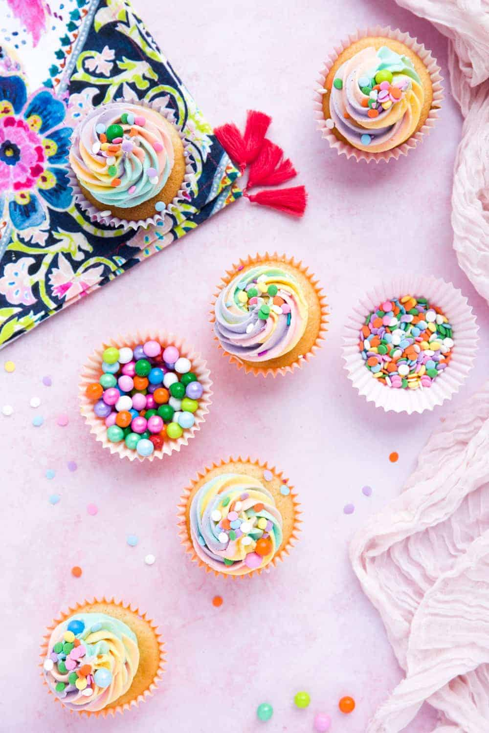 Overhead shot of cupcakes with rainbow coloured icing. There is a cupcake liner filled with round colourful sprinkles and a brightly coloured napkin.