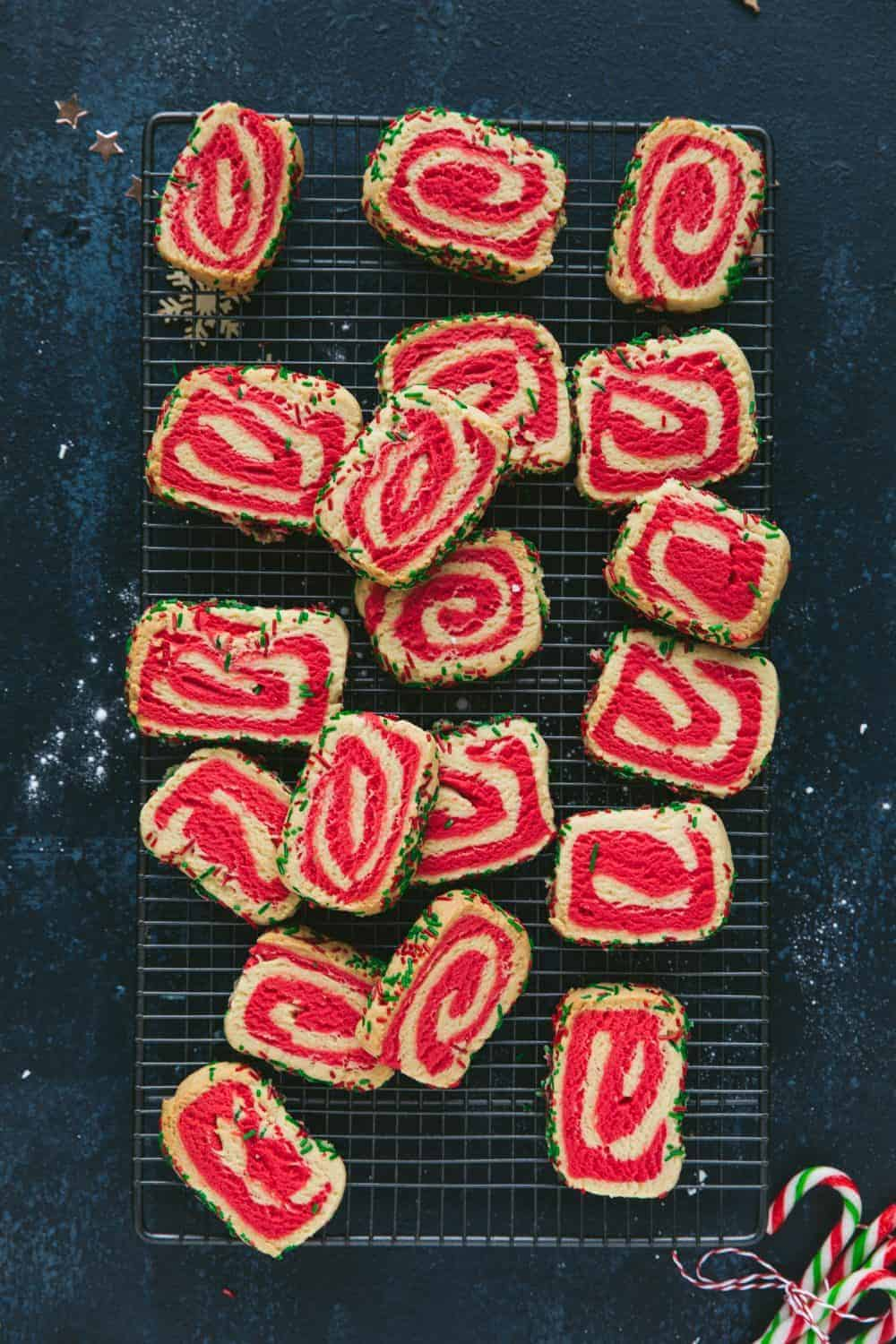 Red and white swirl cookies on a metal cooling wrack.