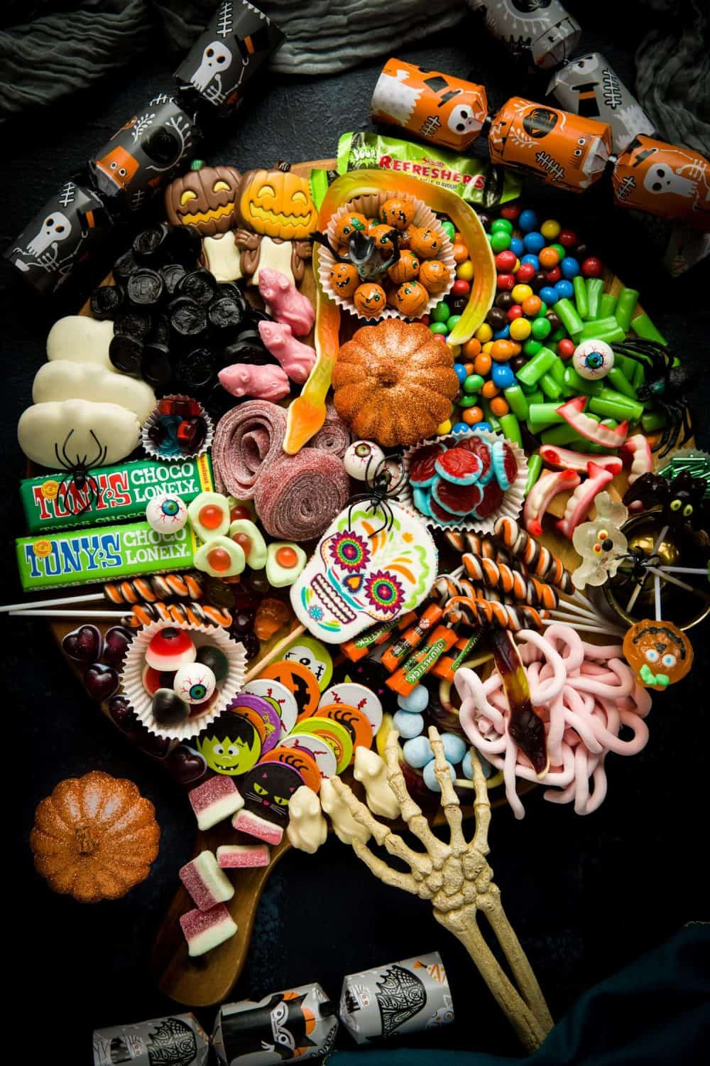 A Halloween Treat Platter filled with a wide variety of sweets, candy and chocolates. It is surrounded by halloween crackers and there is a skeleton hand reaching on to the tray.