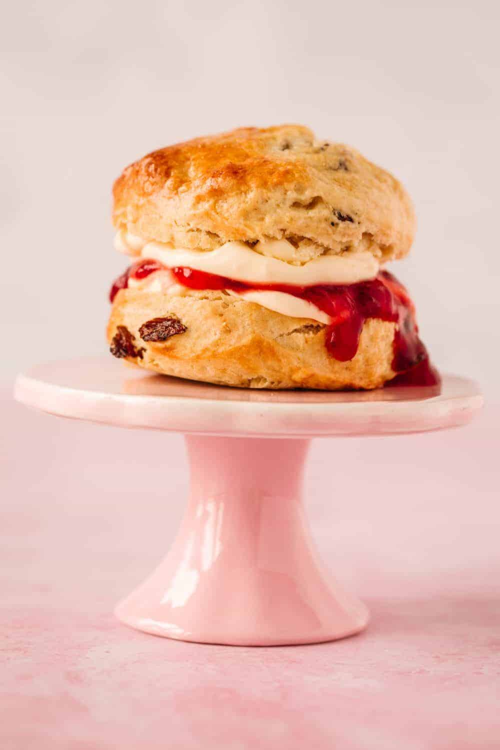A fruit scone on a small pale pink cake stand.