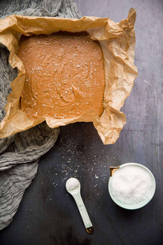 Creamy caramel fudge in a baking tin next to a pot containing sea salt.
