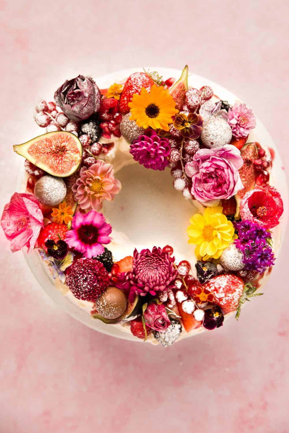 Overhead of a wreath shaped pavlova covered in fruit ad edible flowers.
