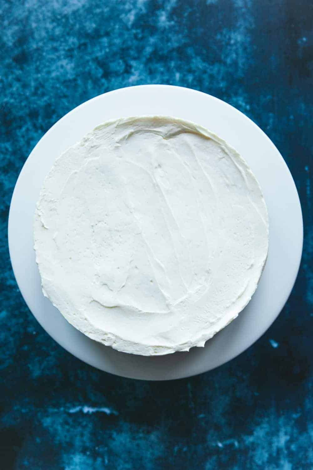 Overhead view of a round undecorated cheesecake. The filling is white in colour.