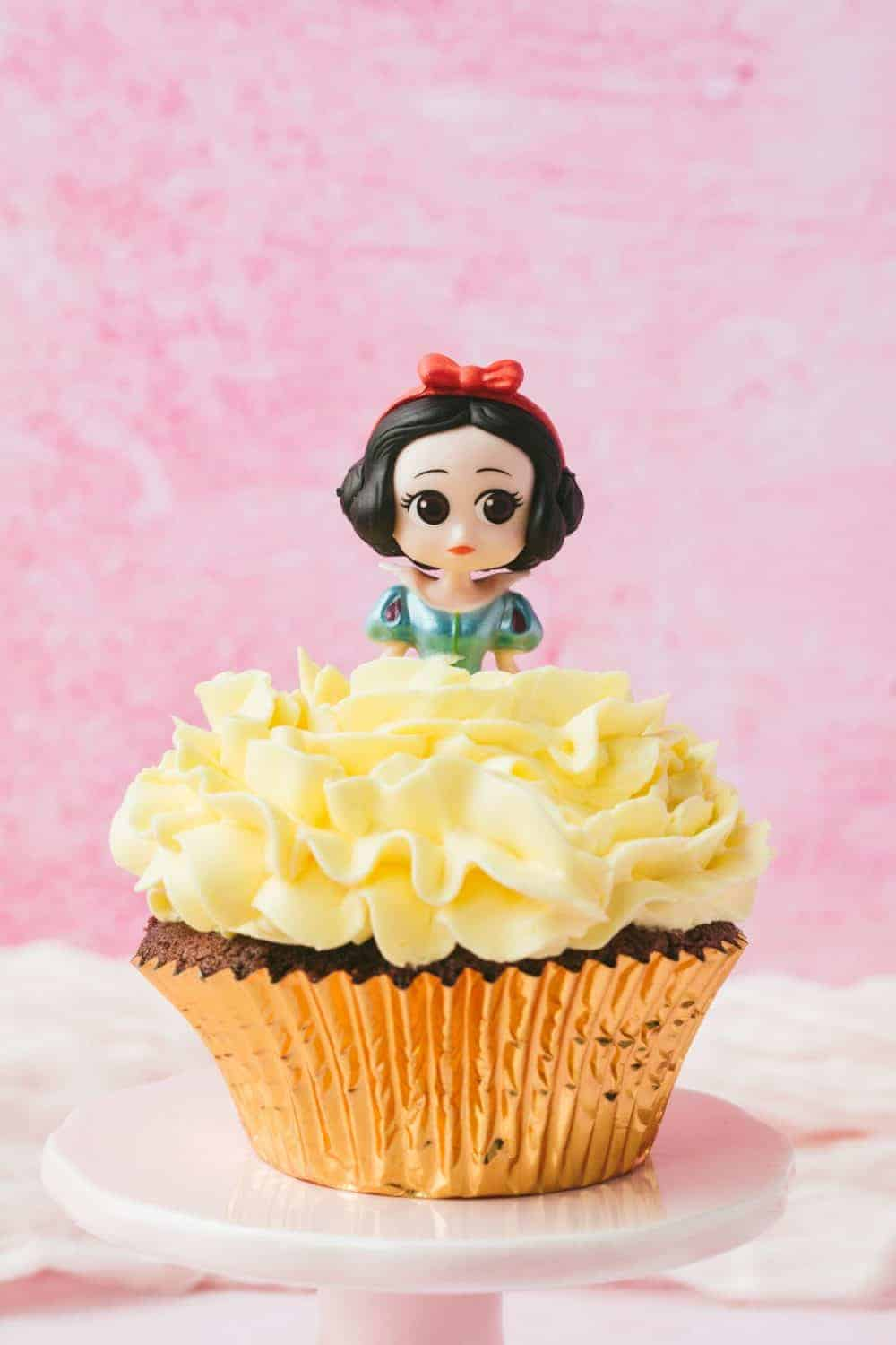 A snow white cupcake with yellow icing.