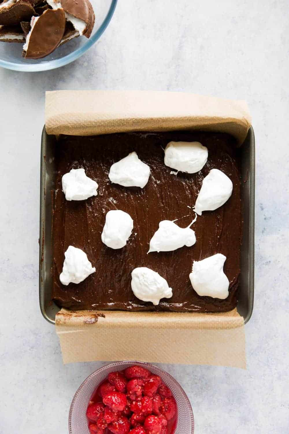 Brownie batter with marshmallow fluff spooned over the top.