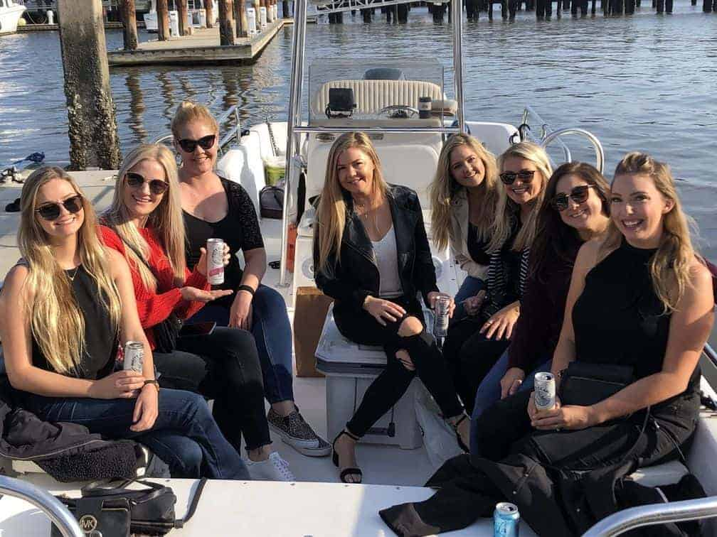 Women dressed up enjoying their White Claws on the boat. Charleston booze cruise bachelorette