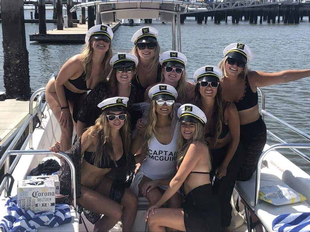 Group picture of women all wearing sunglasses and captains hat. Charleston bachelorette party boat