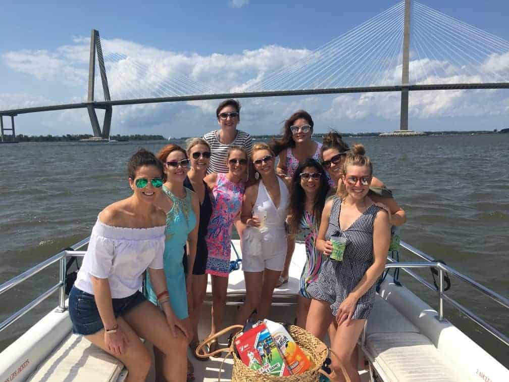 Group of women gathered for a group picture on the boat in front of the bridge. Charleston booze cruise bachelorette