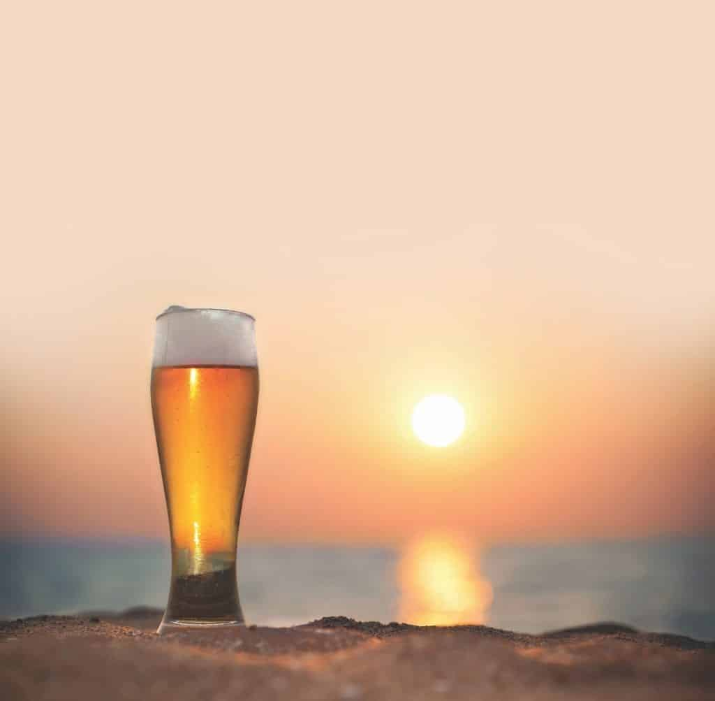 A beer on the beach during sunset.
