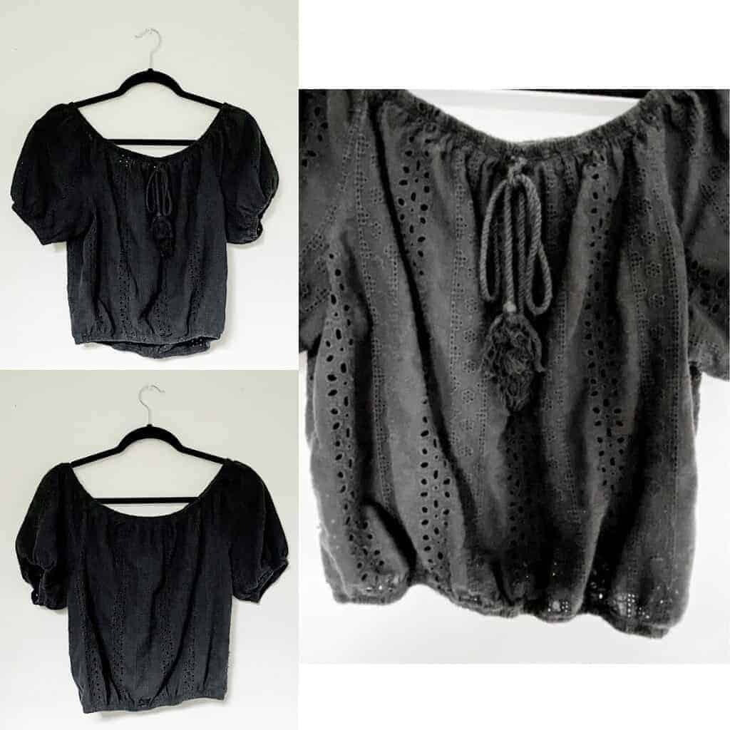 A black eyelet cropped shirt with puff sleeves, elastic around the hems for a tight fit, and a rope tassel tie at the neckline.