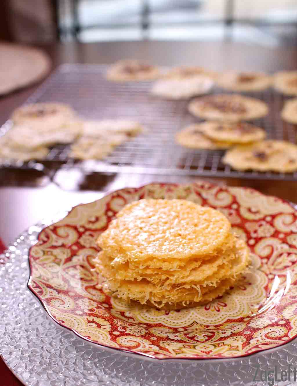 A stack of Parmesan Cheese Crisps on a plate with a cooling rack in the background