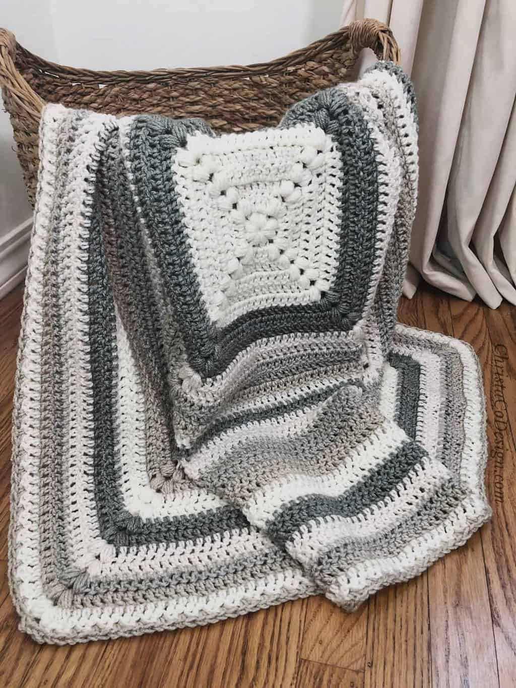 picture of grey and white crochet puff stitch blanket in basket