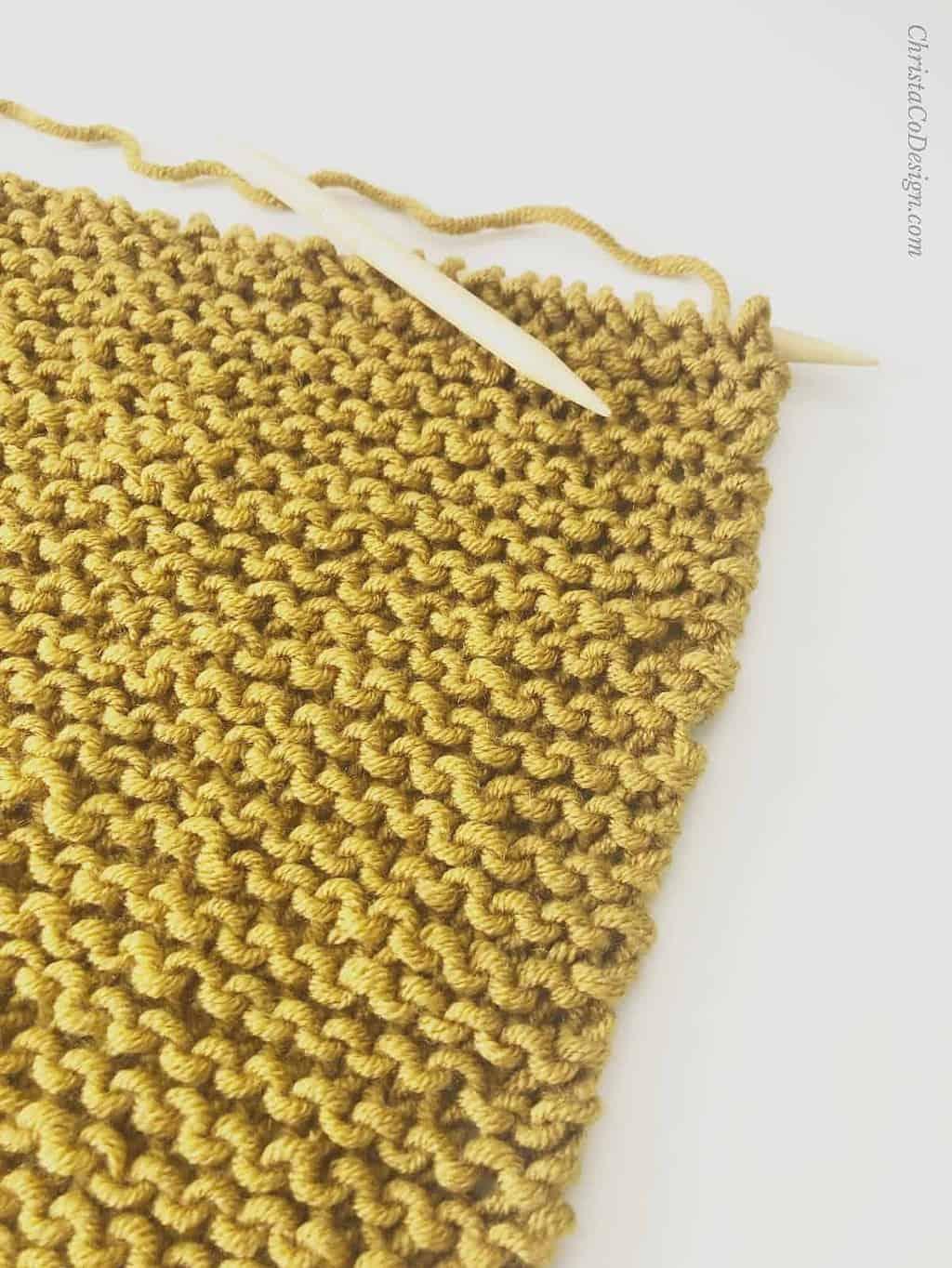 picture of mustard yellow garter stitch shawl on knitting needles