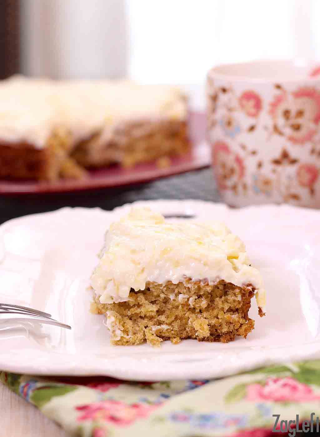 Closeup of a slice of pineapple oat cake with cream cheese frosting on a plate with a floral napkin and a coffee mug in the background