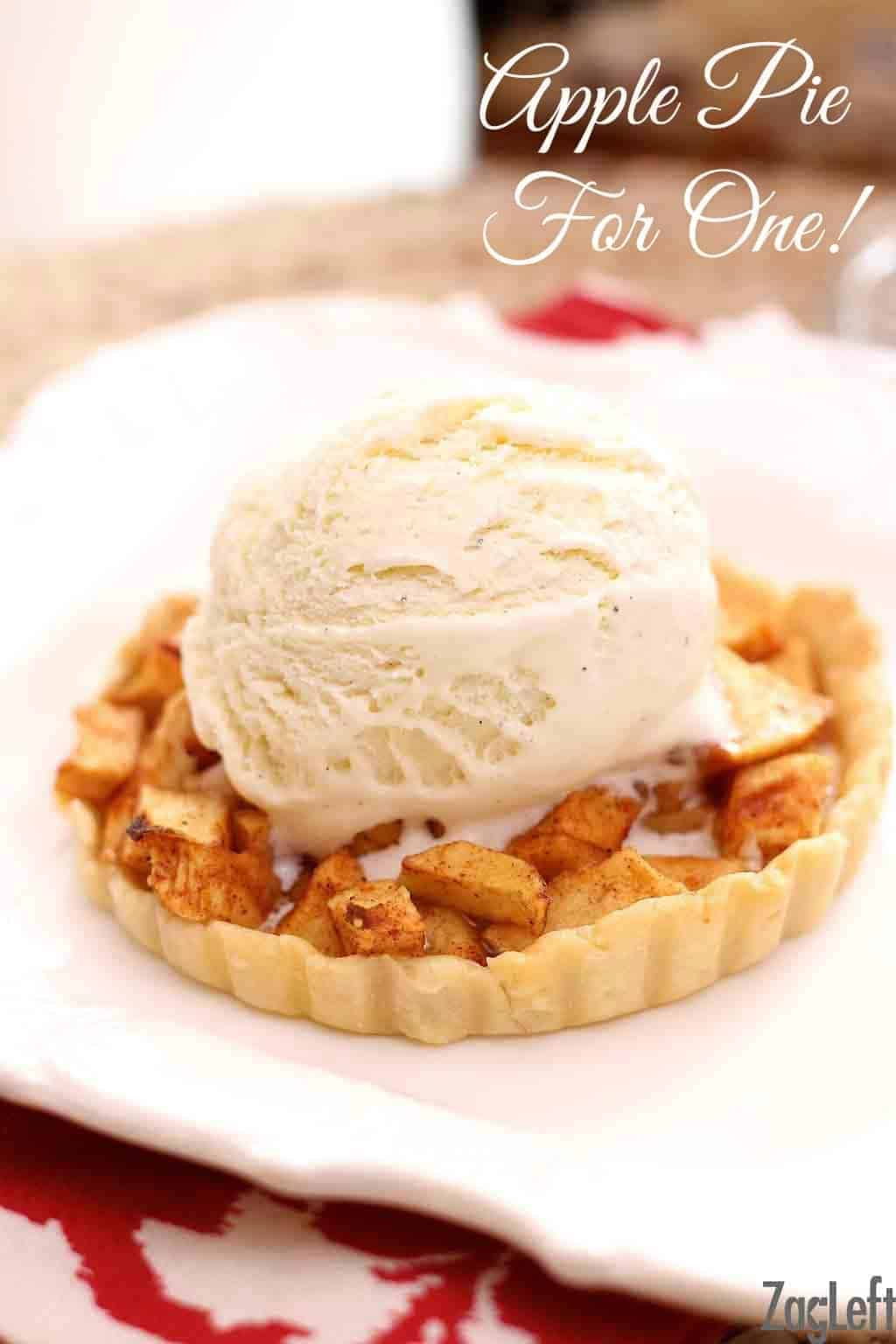 A mini apple pie topped with a scoop of vanilla ice cream