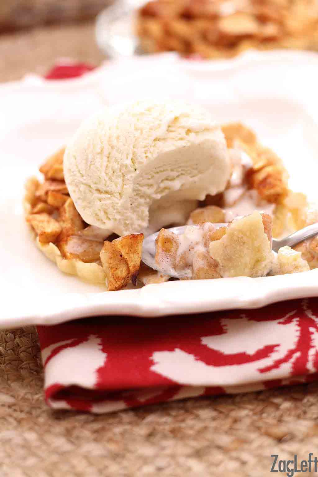 A spoonful of a mini apple pie topped with a scoop of vanilla ice cream