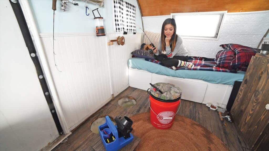 Jenny fishing in the fish house camper.