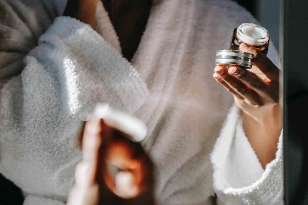 a woman in a white bathrobe holding a jar of face cream