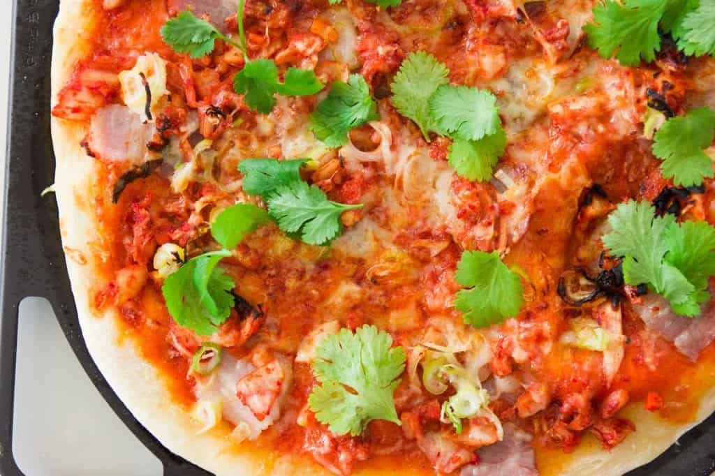 Delicious grilled kimchi and pork belly pizza on top a crisp crust seasoned with spicy gochujang sauce.