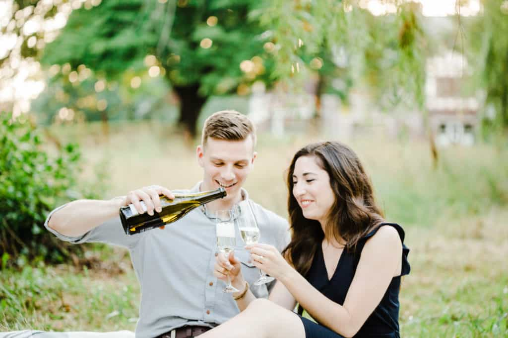 guy is pouring champagne during the engagement session