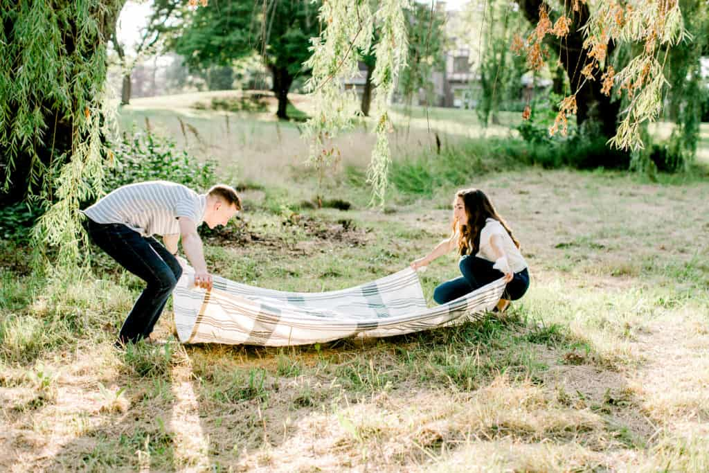 engagement session couple spreading blanket on the ground during golden hour