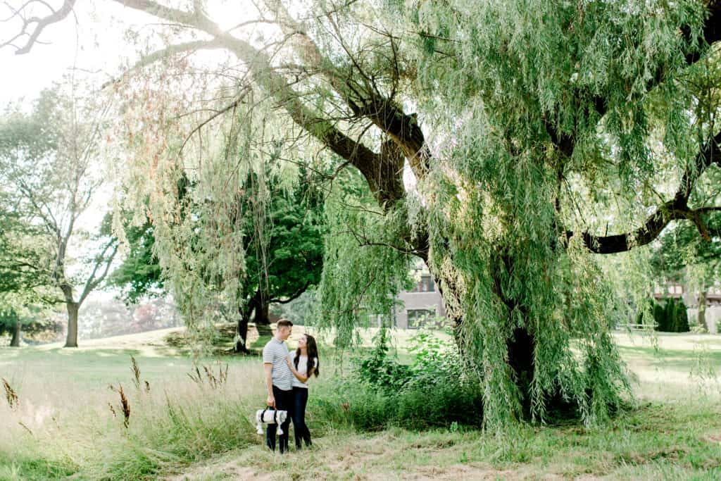 couple standing under weeping willow and looking at each other