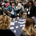 Confab 2019 attendees standing around tables looking at notecards