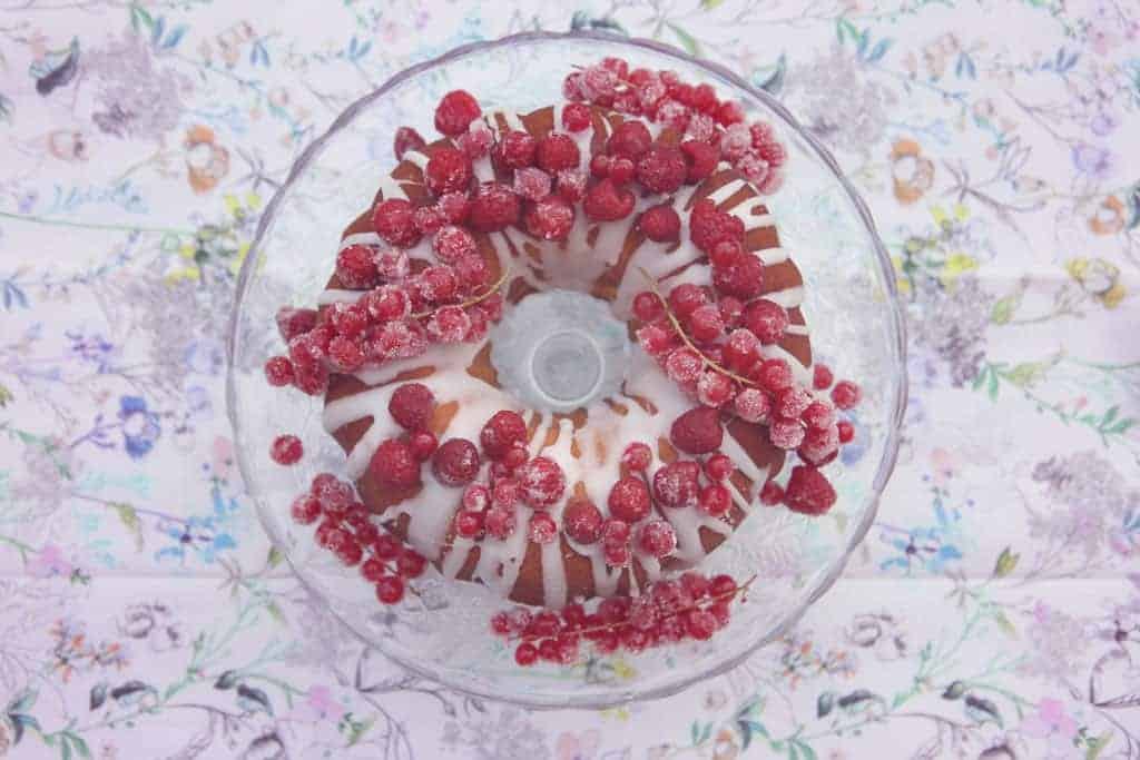 Lemon drizzle bundt cake decorated with raspberries and redcurrants