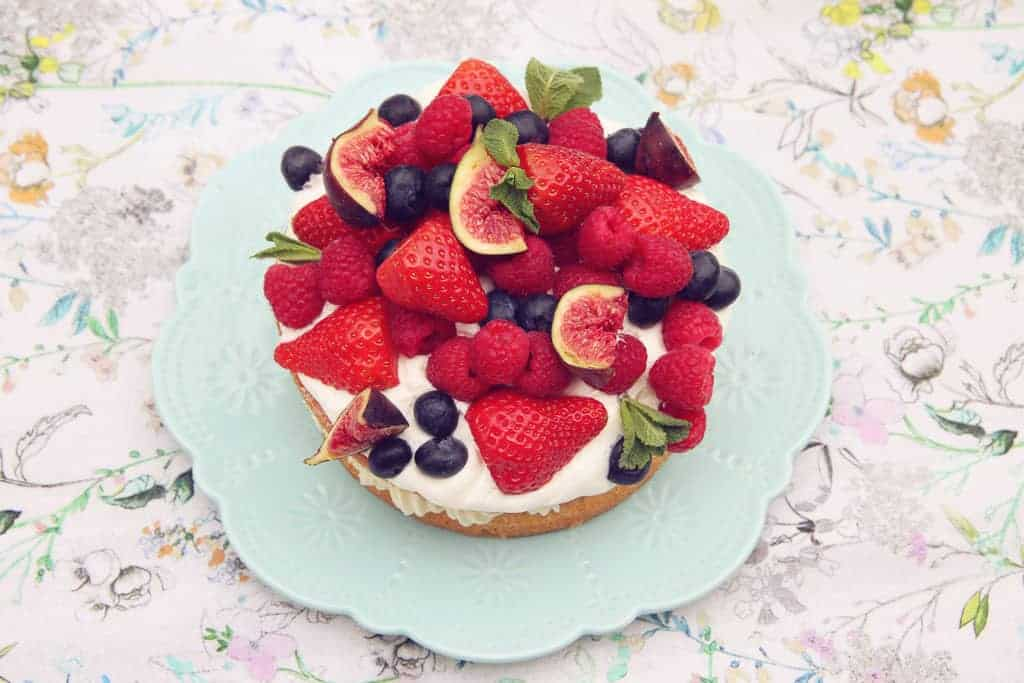 A birds eye view of a victoria sponge cake filled with jam and buttercream icing and topped with fresh cream and a variety of fruit