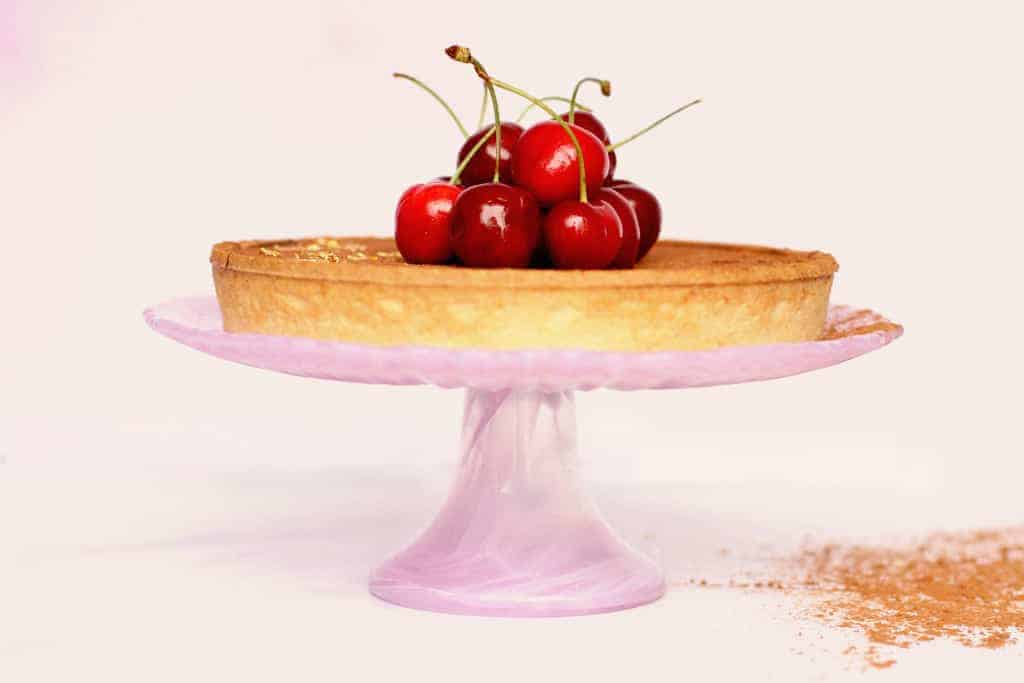 Side view of a salted caramel and chocolate tart with cherries on top