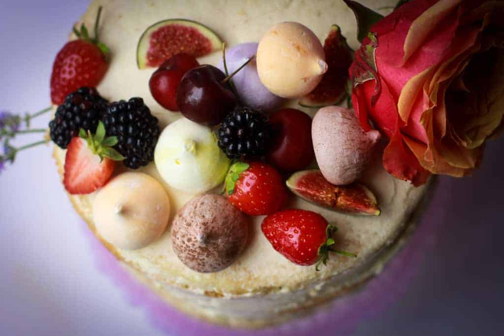 Overhead shot of a vanilla naked cake with meringues, fruit and fresh flowers