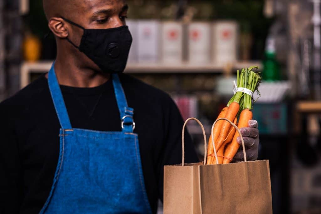 A male Black worker bags groceries. (Photo by Matthew Henry from Burst)