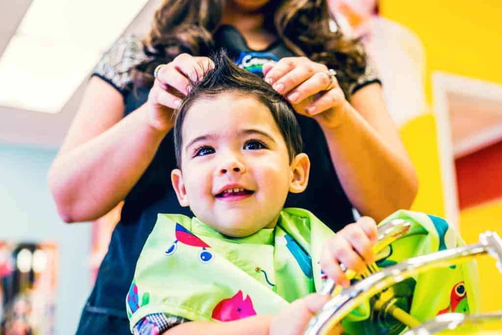 happy little boy at pigtails & crewcuts childrens hair salon