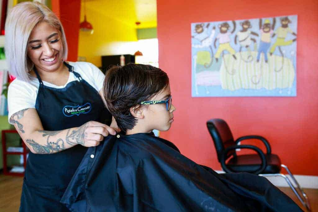 stylist cutting boy's hair in pigtails & crewcuts franchise
