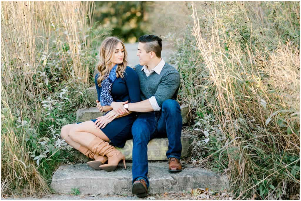 engaged couple sitting on the stairs looking at each other during an engagement session in Chicago  Lincoln Park zoo photographer by Bozena Voytko Photography