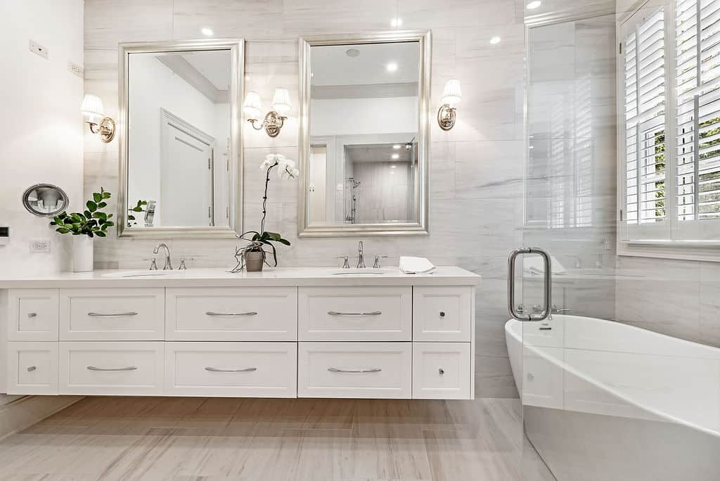bathroom with double vanity top with white drawers golden mirrors, and light fixtures by Chicago interior photographer bozena voytko