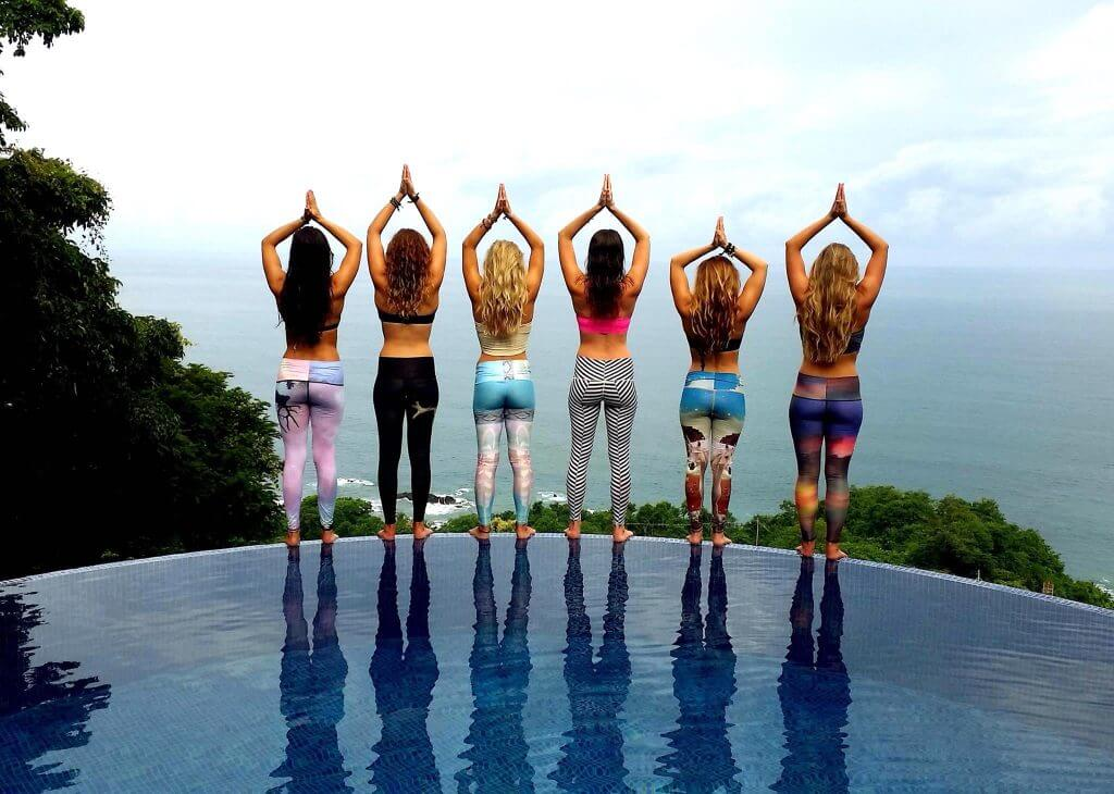 group yoga pose by infinity pool above ocean