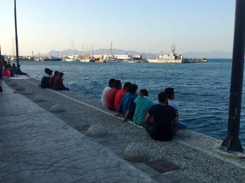 Flüchtlinge auf der Hafenmauer in Kos, Griechenland