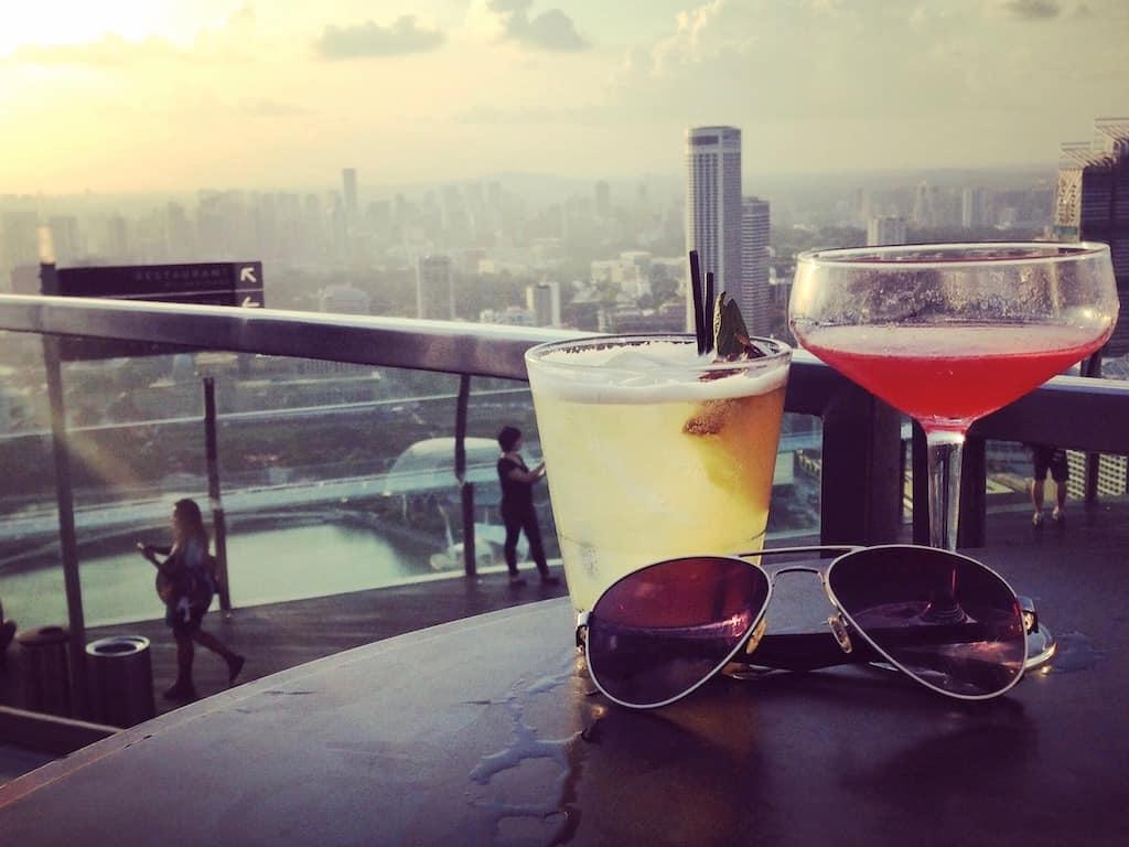 Zwei Alleinreisende genießen zusammen Cocktails in Singapur