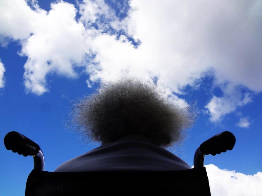 person in wheelchair looking at sky