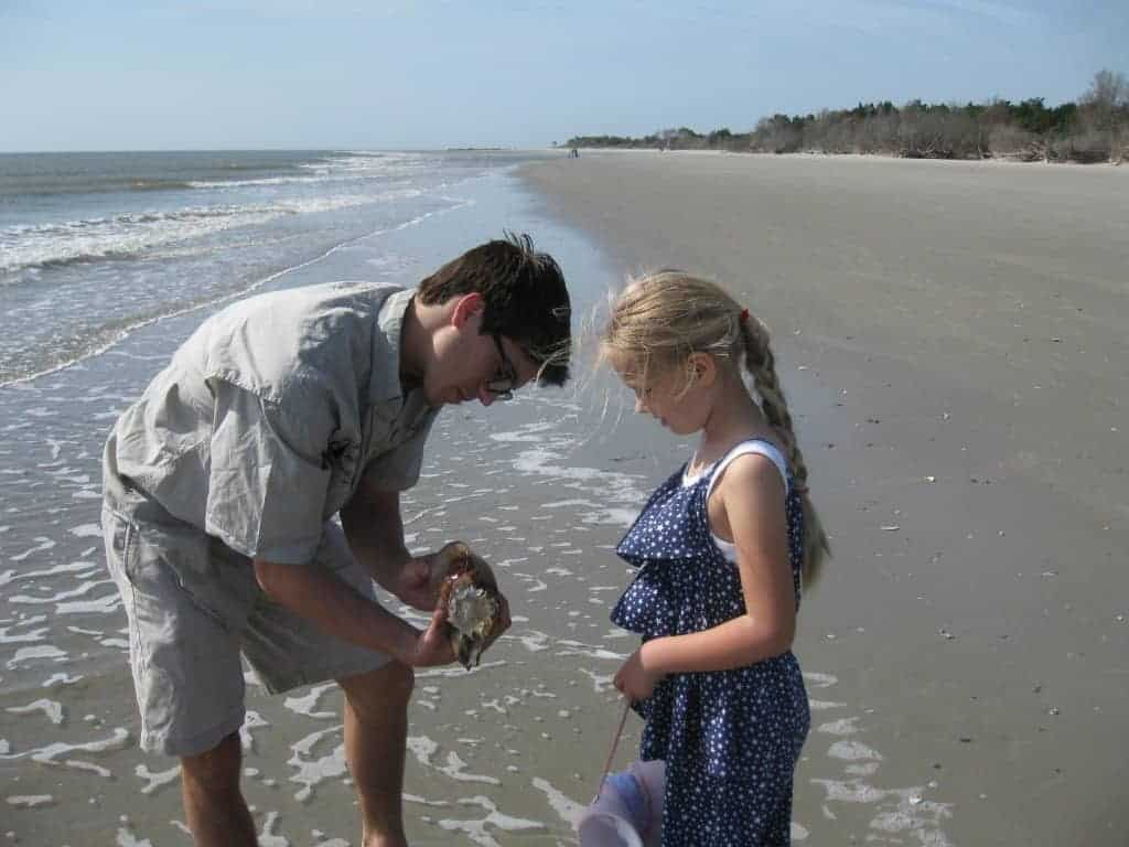 Boy shows girl what he found on the shore. Nature boat tours Charleston