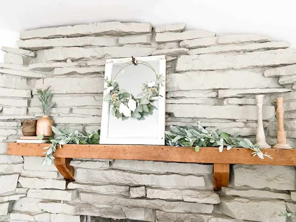 This image shows a gray stone fireplace with a wood mantel decorated with a garland, a window mirror, a spring hoop wreath, some wooden candle holders, and some wooden vases on top of old books.