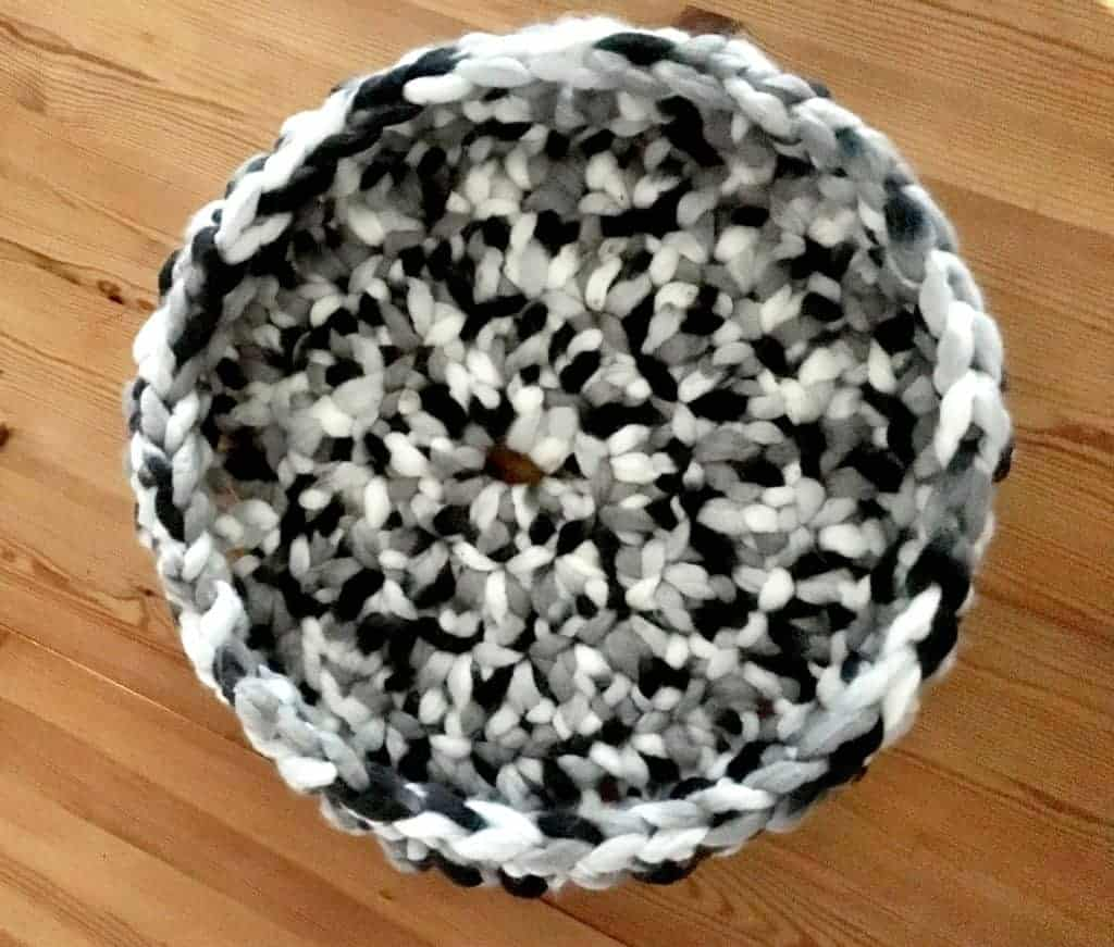 Finished crocheted cat bed made with black, white and gray yarn.