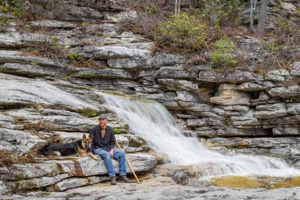 A man and a German Shepherd dog sitting next to a waterfall in the Hudson Valley New York
