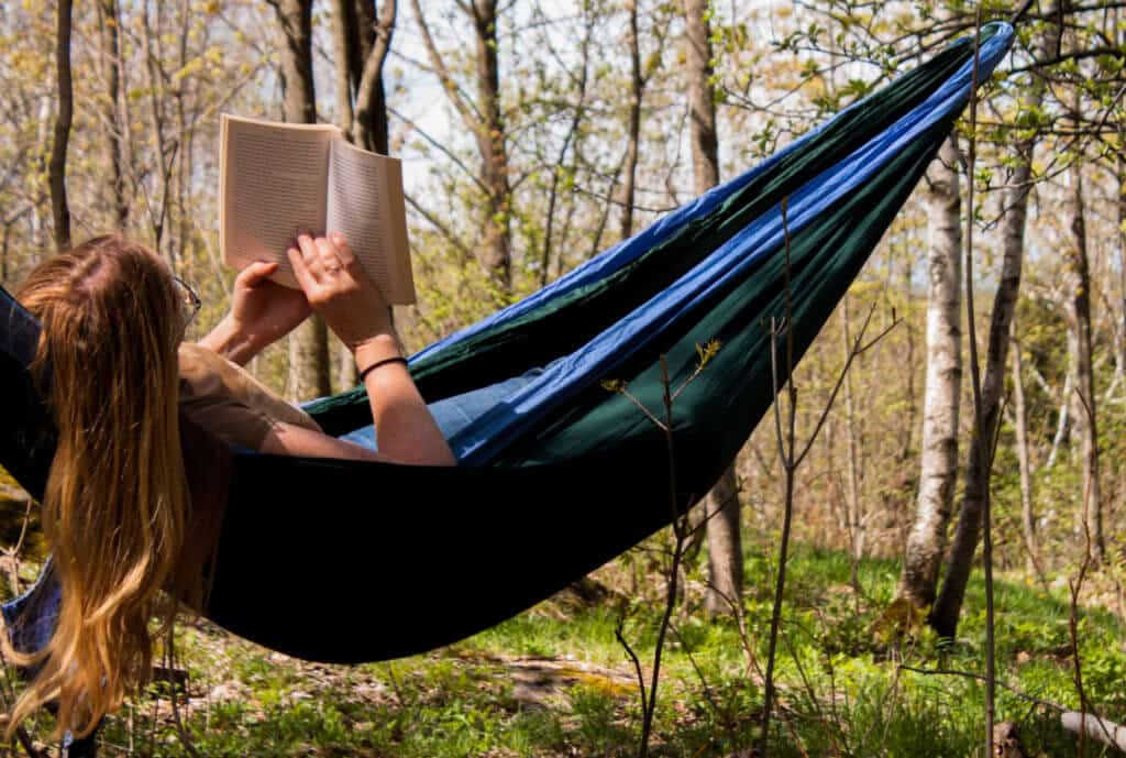 a woman relaxes in a hammock reading a book.