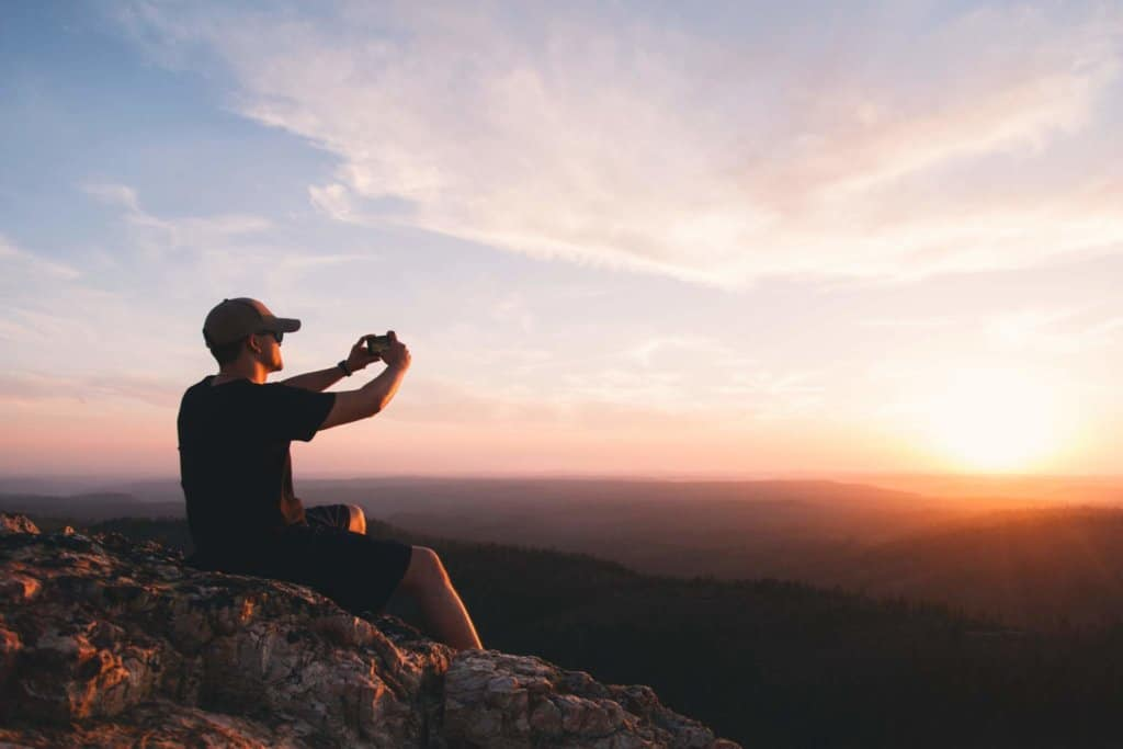 A man sits on a rock facing the setting sun holding a smartphone.