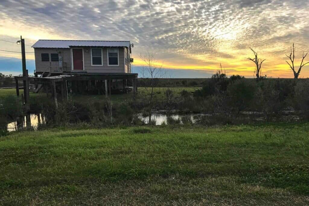 Best Winter Road Trips: A Louisiana sunset featuring a house on stilts in the bayou.